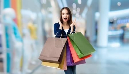Beautiful woman in casual clothing with shopping bags, at shoppi