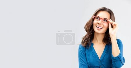 Photo for Portrait of happy smiling young cheerful businesswoman, in glasses, looking up, over grey background, with blank copyspace area for advertising slogan or text message. Caucasian brunette model in business concept studio shot. - Royalty Free Image