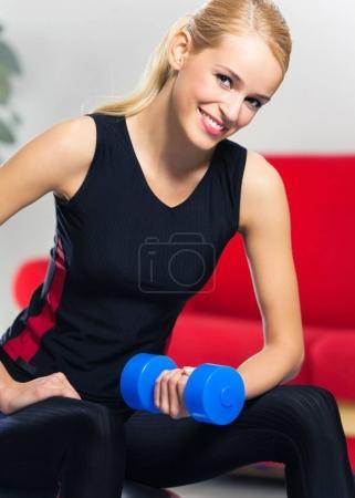 Photo pour Portrait de jeune femme en vêtements de sport, faire des exercices de fitness avec haltères sur ballon fit, à l'intérieur. Mode de vie sain, lossing poids et sportives thème concept abattu. - image libre de droit