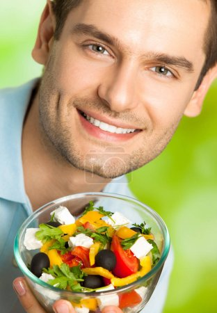 Photo for Portrait of young happy smiling man with plate of salad, outdoors. Healthy eating and diet theme concept. - Royalty Free Image