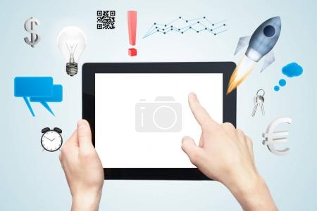 Hands holding and pointing at tablet with empty white screen and creative business icons on gray background. Mock up, Startup concept. 3D Rendering