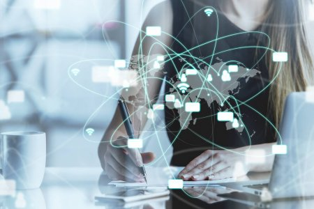 Woman using laptop and doing paperwork at workplace with abstract net map hologram. Networking concept