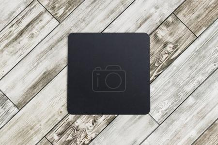 Square coaster on wooden background