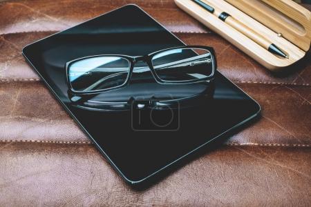 Photo pour Vue du dessus de la tablette, des lunettes et des fournitures placées sur le dessus du bureau en cuir. Gadget et concept de communication. Maquette - image libre de droit