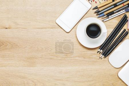 Photo for Top view of modern wooden office tabletop with various stationery tools, coffee cup and devices. Copy space - Royalty Free Image