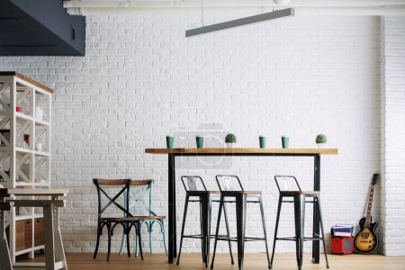 Photo for Contemporary interior with table, chairs and other furniture, white brick wall and guitar. Hobby, home, leisure concept - Royalty Free Image