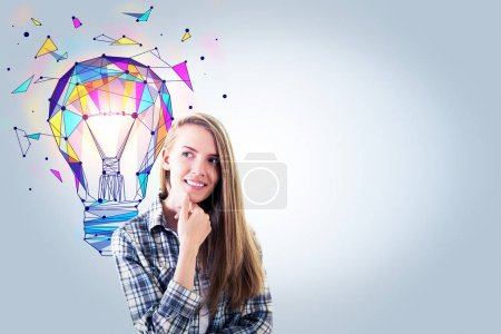 Photo for Portrait of attractive smiling european female on grey background with copy space and polygonal lamp. Idea and creativity concept - Royalty Free Image