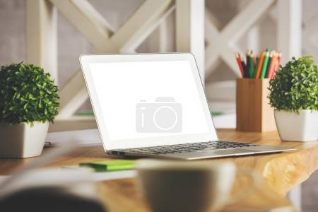 Photo for Close up of creative designer workplace with empty white laptop screen, coffee cup, supplies and other items. Workplace concept. Mock up - Royalty Free Image