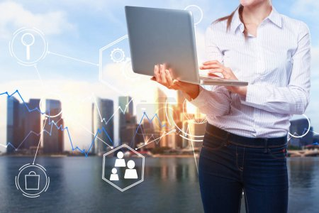 Photo for Female using laptop on abstract city background with digital business hologram. Finance and communication concept. Double exposure - Royalty Free Image