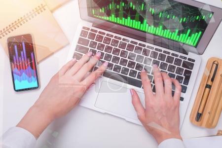 Photo pour Mains en utilisant un ordinateur portable avec un tableau d'affaires numérique à l'écran, placé sur le bureau. Croissance financière et concept de vente. Double exposition - image libre de droit
