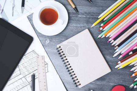 Photo for Top view of modern messy workplace with various, supplies, devices and sketches. Close up - Royalty Free Image