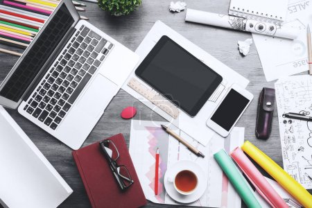 Photo for Top view of creative messy table with various, supplies, devices and sketches. Close up - Royalty Free Image