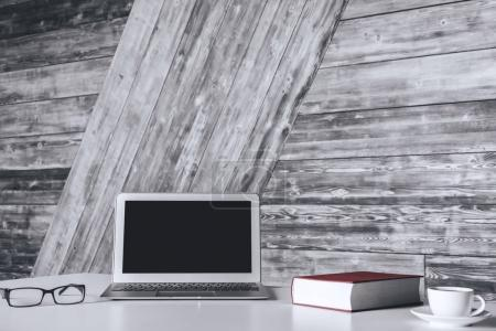 White desk top with blank laptop