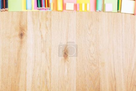Wooden office desktop with colorful supplies
