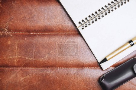 Photo pour Vue de dessus de bureau en cuir marron avec des fournitures, autres objets et espace de copie. Maquette - image libre de droit