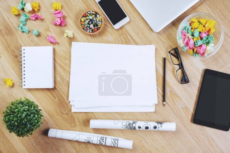 Photo for Top view of wooden office workspace with blank notepad, smartphone, tablet and other items. Mock up - Royalty Free Image
