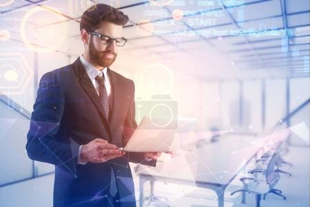 Photo pour Homme d'affaires utilisant un ordinateur portable sur fond abstrait de salle de réunion avec une interface digtale lumineuse. Concept d'avenir et innovation. Double exposition - image libre de droit