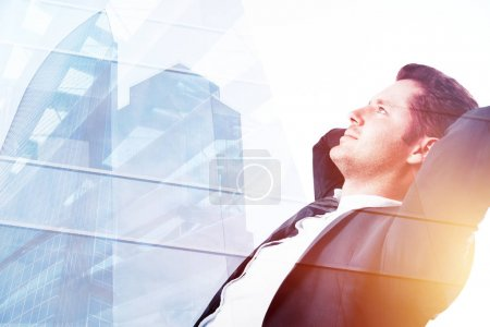 Photo for Side portrait of relaxing young businessman on abstract city background with sunlight and copy space. Success and employment concept. Double exposure - Royalty Free Image