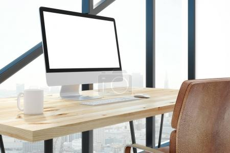 Modern office with empty white computer screen