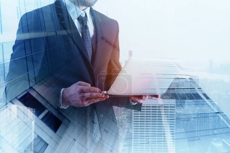 Photo for Man using laptop on abstract city background with copy space and daylight. Double exposure - Royalty Free Image