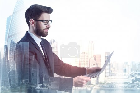 Photo for Handsome young european businessman using laptop on abstract city background with copy space. Technology and communication concept. Double exposure - Royalty Free Image