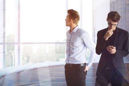 Photo pour Deux beaux hommes d'affaires européens utilisant un smartphone ensemble dans un bureau moderne avec vue sur la ville. Travail d'équipe et concept de communication. Double exposition - image libre de droit
