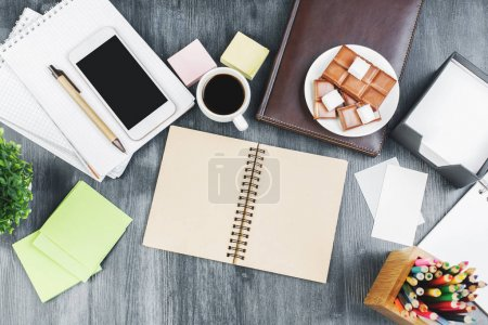 Photo for Top view of modern wooden office desk with empty smartphone screen, supplies, coffee cup and food. Copy space. Work, snack, break, leisure and nutrition concept - Royalty Free Image