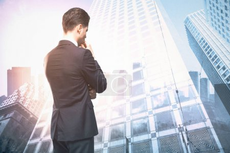 Photo for Young businessman on abstract city background. Success and research concept. Double exposure - Royalty Free Image