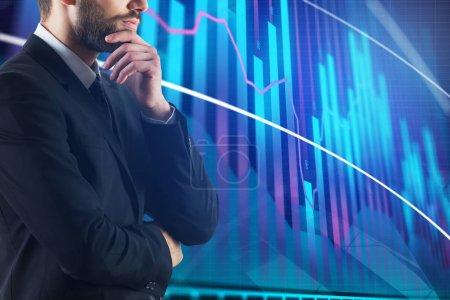 Photo pour Homme d'affaires réfléchi avec graphique forex abstrait. Concept de commerce et de courtier - image libre de droit