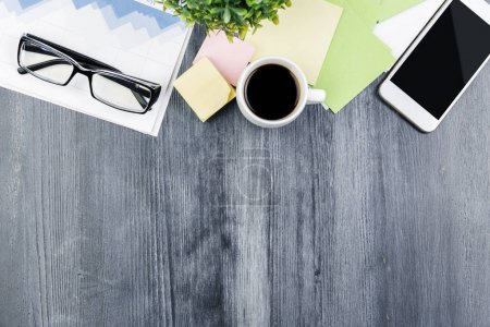 Photo for Top view and close up of gray wooden office tabletop with smartphone, supplies and other items. Mock up - Royalty Free Image