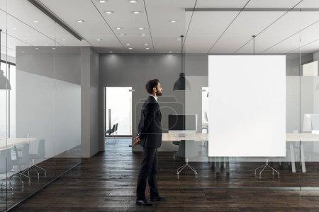 Photo pour Homme d'affaires debout dans l'intérieur de bureau moderne avec bannière vide sur le mur. Rendu 3D - image libre de droit
