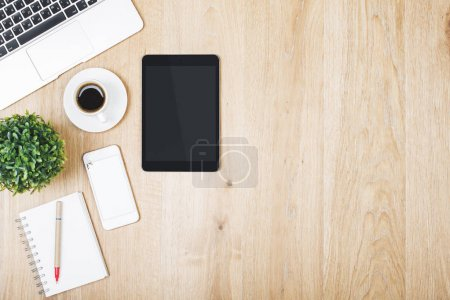 Photo for Close up of modern office desk top with empty tablet, smartphone and laptop, supplies and other items with copy space. Mock up, Above view - Royalty Free Image