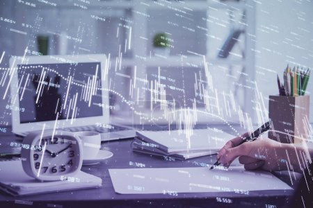 Photo for Financial graph displayed on womans hand taking notes background. Concept of research. Multi exposure - Royalty Free Image