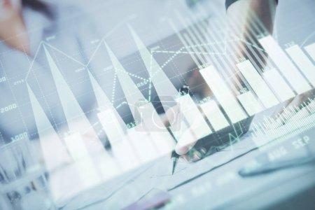 Photo pour Une femme remet des informations d'écriture au sujet du marché boursier dans le bloc-notes. Hologrammes de diagramme de Forex devant. Concept de recherche. surimpression - image libre de droit