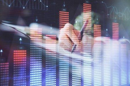 Photo pour Graphique Forex financier affiché sur les mains en prenant des notes de fond. Concept de recherche. Exposition multiple - image libre de droit