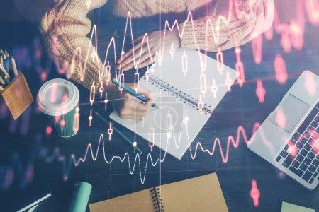Photo pour Graphique de forex sur la main prenant des notes de fond. Concept de recherche. surimpression - image libre de droit