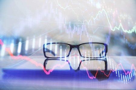 Photo pour Hologramme graphique financier avec des lunettes sur le fond de la table. Concept d'entreprise. Double exposition. - image libre de droit