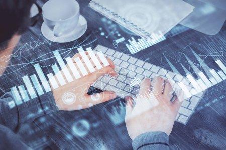 Photo pour Multi exposition du graphique avec l'homme tapant sur l'ordinateur dans le bureau sur l'arrière-plan. Concept de travail acharné. - image libre de droit