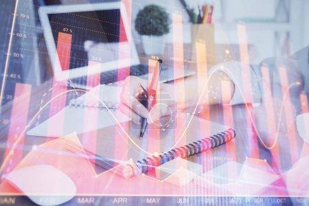Photo pour Graphiques financiers affichés sur la main womans prendre des notes de fond. Concept de recherche. surimpression - image libre de droit