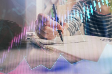 Photo for Financial forex graph drawn over hands taking notes background. Concept of research. Double exposure - Royalty Free Image
