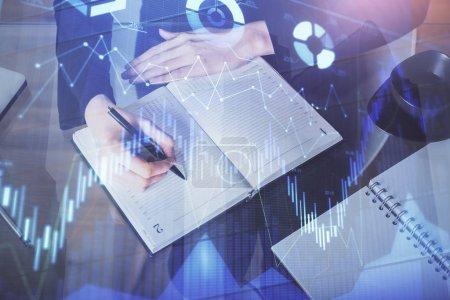 Photo pour Hologramme de diagramme de forex sur la main prenant des notes de fond. Concept d'analyse. Multi exposition - image libre de droit