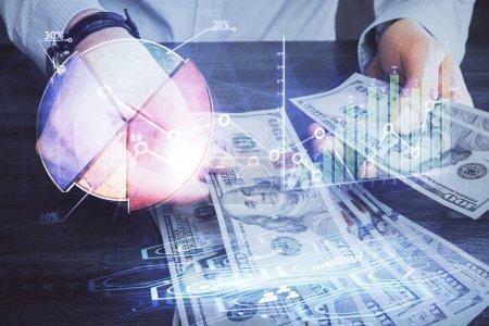 Foto de Multiexposición de holograma de dibujo de gráficos financieros y letras en dólares estadounidenses y manos del hombre. Concepto de análisis. - Imagen libre de derechos