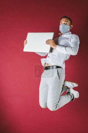 Photo pour Jeune homme en chemise blanche et masque sur son visage sauta, pleine longueur avec un ordinateur dans les mains, sur un fond rouge. Pandimie, isolement - image libre de droit