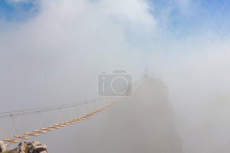 Photo pour Homme traversant le gouffre sur le pont suspendu dans le brouillard (se concentrer sur le milieu du pont ) - image libre de droit