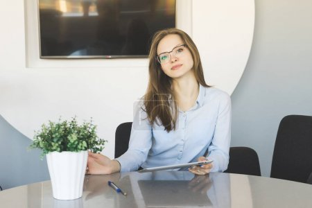 girl sitting at table with tablet in hands in office and looking at camera