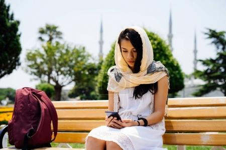 Muslim girl turkish sitting on a bench in the park and looking for something in the phone