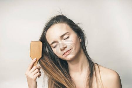 girl with closed eyes combing her hair