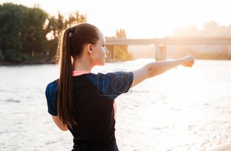 Athletic girl kneads muscles by the river in the r...