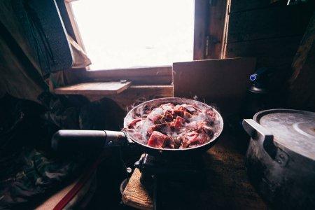 Photo pour Dans le pavillon de chasse du éleveur de rennes, la viande de cerf est frite dans une poêle - image libre de droit
