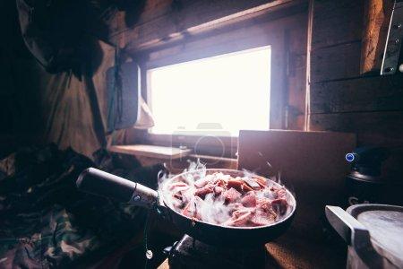 Photo pour Dans la cabane du chasseur, la viande fraîche de cerf est frite dans une poêle - image libre de droit